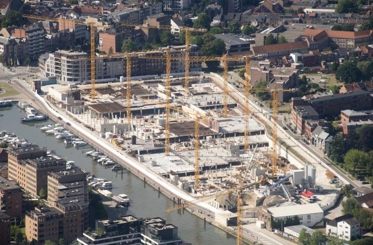 Osiem żurawi WOLFF buduje nowoczesną dzielnicę Quartier Bleu wsąsiedztwie mariny Hasselt nazlecenie STRABAG Belgium NV