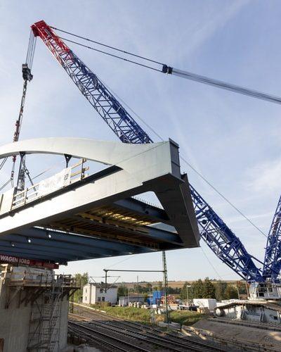 Żuraw gąsienicowy Liebherr podnosi łukowy most ważący 242 tony